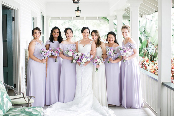 bridesmaids in mismatched light purple bridesmaid dresses and bouquets maid of honor in white dress