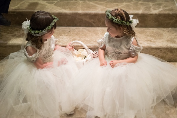 flower girls with tulle skirts, greenery crown, sitting on steps before ceremony