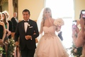 bride in alyne ball gown with large belt, blusher veil, walks down aisle with father in tux