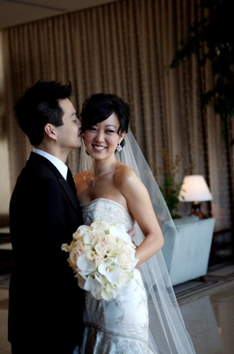 Bride in a beaded Lazaro gown and groom in a black tuxedo