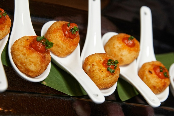small croquette hors d'oeuvres rolled into balls and served on big spoons with sauce and garnish