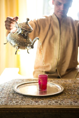 Man in Moroccan clothes pours tea from a silver teapot to a fuchsia class at engagement party