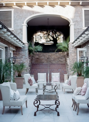 Outdoor wedding lounge area with white chairs, ruffled pillows in pink and ivory