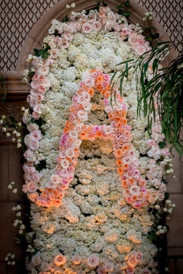 White hydrangea flower wall with pink and orange roses forming initial letter A