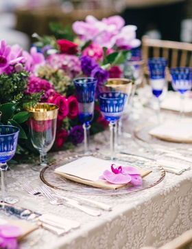 Outdoor wedding with colorful low flower centerpieces, clear gold rim charger with orchid bloom