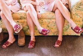 bridesmaids sit sporting pink and purple bath slippers and robes
