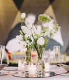 simple reception centerpieces, white flowers in bud vases on mirror with candles