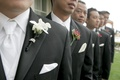 Groom in pinstripe tuxedo and white tie with groomsmen in grey tuxedos