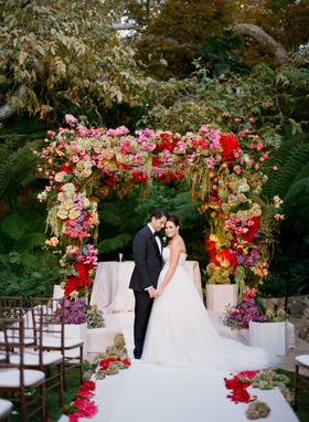 Bride and groom hold hands under colorful Jewish wedding chuppah at Hotel Bel-Air Swan Lake