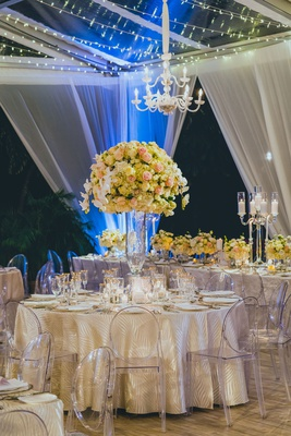 tented reception with ghost chairs, patterned linens, large centerpieces with roses and orchids