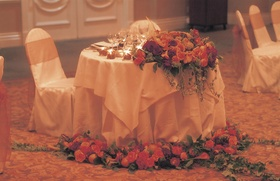 sweetheart table covered in white linens and orange flowers