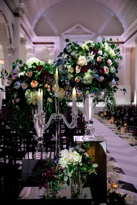 Crystal candelabra on mirror riser with small flower arrangements and glass vases flowers by cina