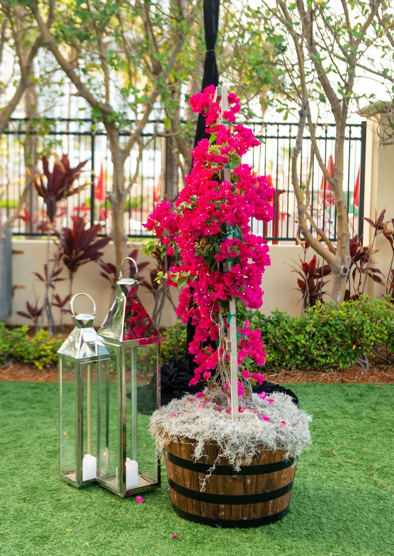 wedding reception tent green lawn wood basket with pink bougainvillea flowers and silver lanterns