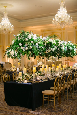 wedding reception ballroom carpet navy blue linen gold chairs candles tall centerpieces chandelier