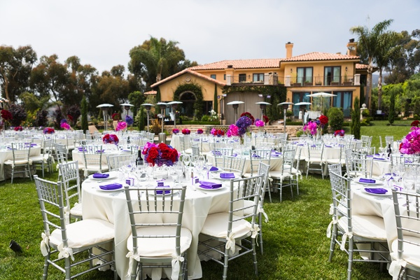 white tables with purple napkins and pink centerpieces