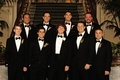 groom and groomsmen in tuxedos with colorful calla lily boutonnieres