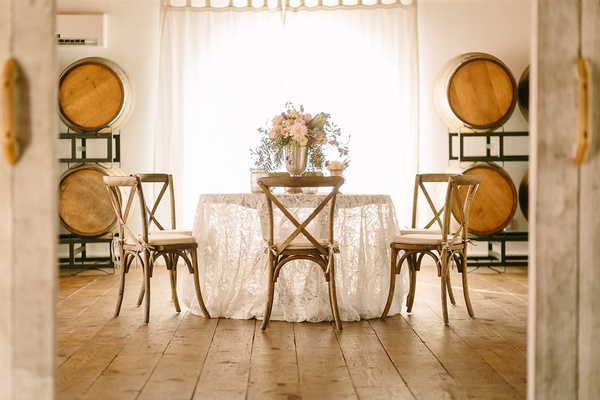round tablescape wine barrels wood faux wedding party styled shoot rustic event lace linen florals