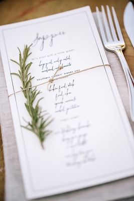 White menu cards with calligraphy and herbs
