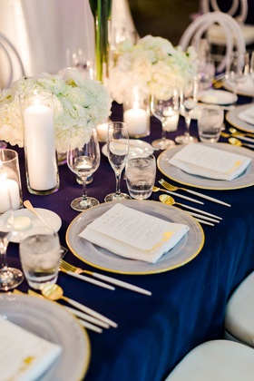 white hydrangea low centerpiece gold rim charger white gold flatware candles in vases blue linen