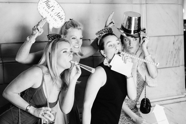 black and white photo of wedding guests in photo booth with noise makers hats and signage