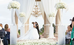 bride groom kiss done white pillars tall arrangements petals chandelier pelican hill newport beach