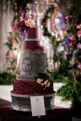 dark and moody oxblood wedding cake with black tier with spindly rose pattern and monogram