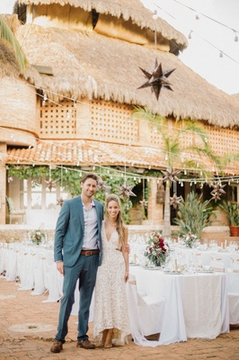 Bride and groom at welcome party rehearsal dinner destination wedding in Mexico thatched roof