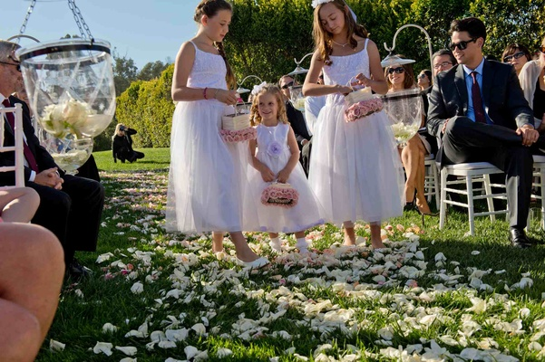 Three flower girls walk down flower petal aisle