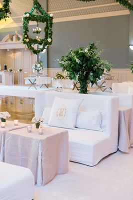 Wedding reception lounge space white lounge furniture table greenery lanterns dance floor