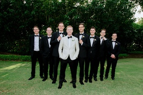 groom in white tuxedo jacket black bow tie groomsmen in tuxes hawaii wedding