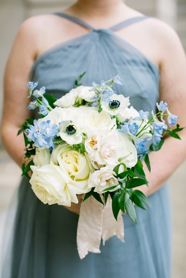 bridesmaid in blue dress holding white rose anemone blue flower greenery bouquet with ribbon wrap