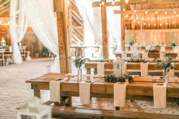 Rustic barn wedding wood picnic tables and benches low greenery flower arrangements lanterns white