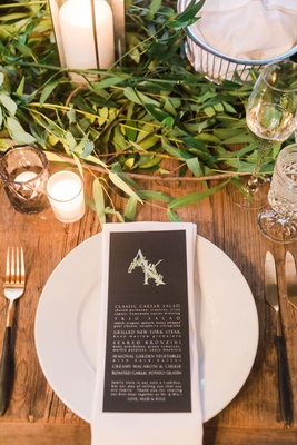 Wood table greenery with black menu card leaf monogram on top white plate wood table black gold fork