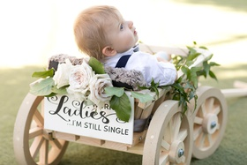 "baby ring bearer in wooden wagon with sign reading ""don't worry ladies, I'm still single"""