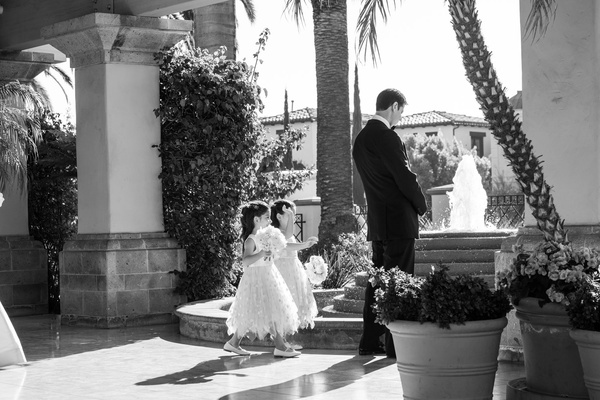 Black and white photo of two maid of honor twin daughters walking up to groom for first look