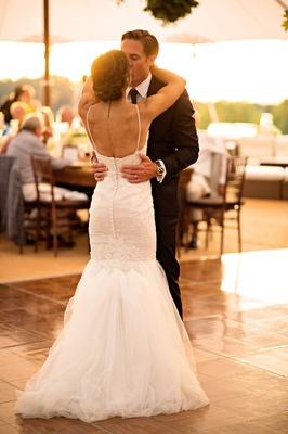Bride in Berta Bridal gown kisses groom in blue Ralph Lauren tuxedo during first dance