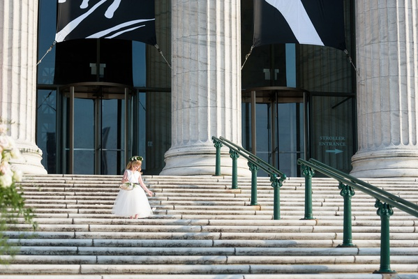 flower girl in white dress and flower crown walking down steps of the field museum chicago wedding