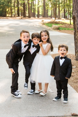 Flower girl in white dress and three ring bearers in little tuxedos bow ties and converse sneakers