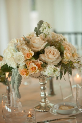 centerpieces with blush roses, dusty miller, and eucalyptus in a silver mercury votive