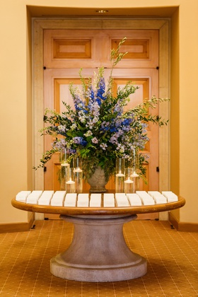 escort card table with large display of bright blue and light periwinkle flowers, floating candles
