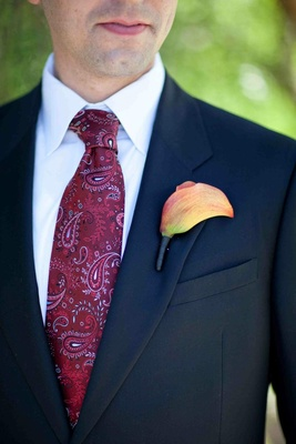 Groom in a dark suit, red paisley tie, and orange calla lily boutonniere