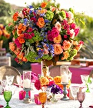 wedding reception lace linen cane chair green orange purple goblets orange pink green flowers