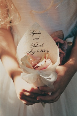 Flower girl holds ivory cone filled with petals