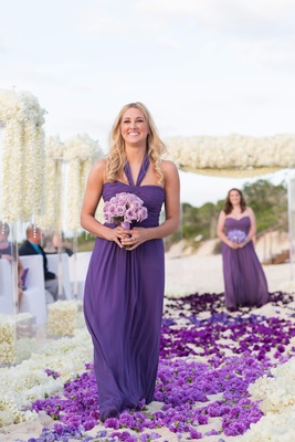 Bridesmaid walking down beach flower petal aisle