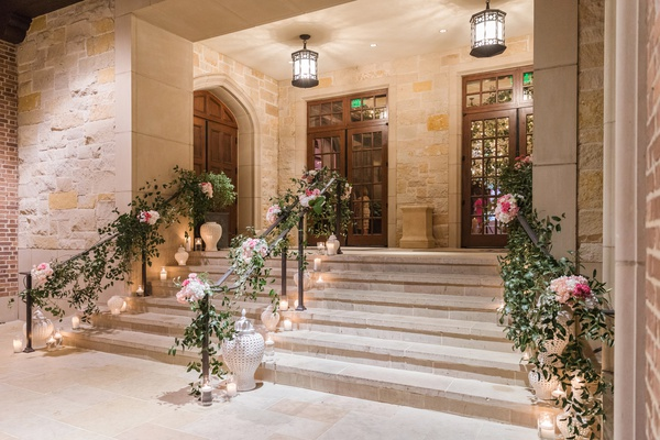 stairway into wedding reception with candles, greenery garland on