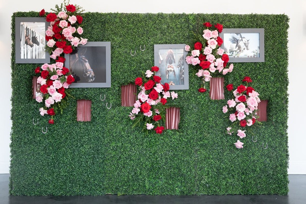 boxwood hedge wall will red and pink roses, photos of horses, windows for hands to serve champagne