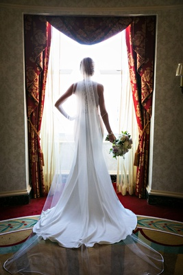 Bride in sleeveless wedding dress tara keely bridal gown long cathedral veil silhouette window shot