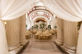 wedding reception gold chairs tall centerpieces greenery white flowers columns white drapery drapes