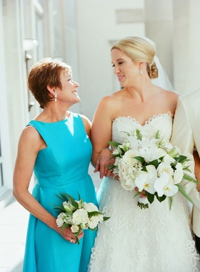 Bride in strapless wedding dress sweetheart neckline with mother of bride in high neck turquoise
