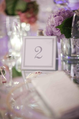 White table number with metallic border on mirror
